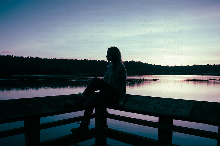Silhouetted woman sitting on a fence against water and subtle sunset in Canada.