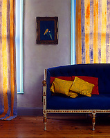 An antique canapé upholstered in an electric blue velvet stands against a set of hand-painted curtains