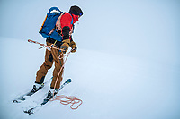 A ski tourer throws a rope ahead while traveling on a glacier in a whiteout. The trick is used when there are crevasses around to see if the rope falls away and to define the contours of the slope. Öztal ski tour, Austria