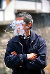 Man smoking pipe; face lost in cloud of smoke; at market in small rural village near Wuxi, China, Asia; 042503