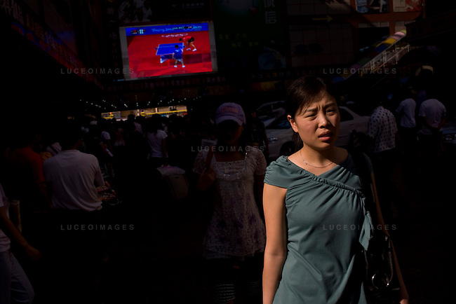 Locals shop at a mall while an Olympic ping pong match is televised in the background in Beijing, China on Friday, August 22, 2008.  Kevin German