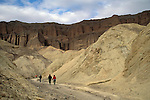 Tourists hiking through hills in valley below Red Cathedral, Golden Canyon, Death Valley National Park, California