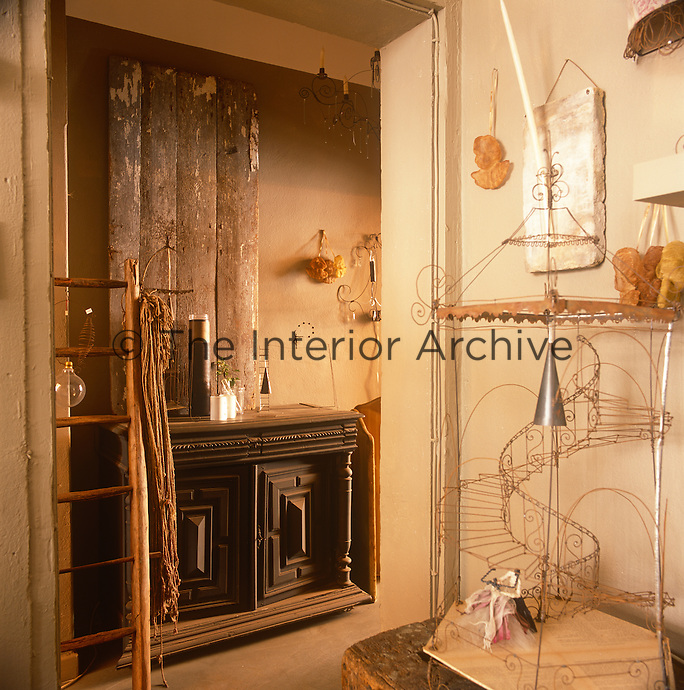 A piece of wire work sculpture stands on a table. An open doorway gives a view through to a heavy wooden sideboard with rough wooden planks as artwork above.