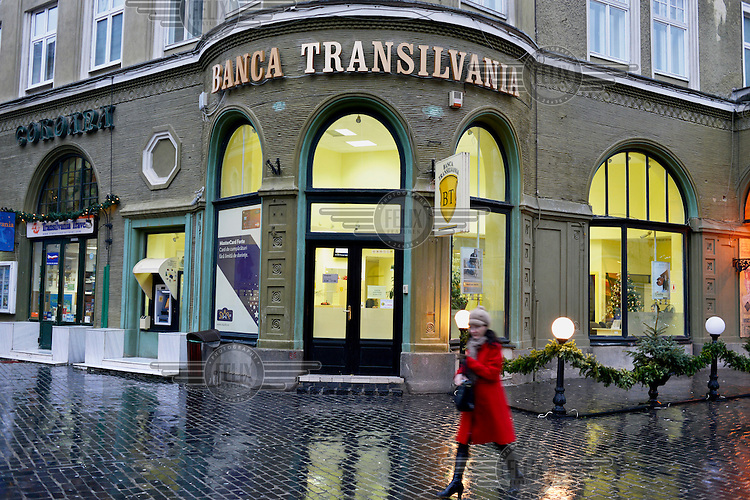 A pedestrian passes in front of a branch of the Bank of Transilvania.