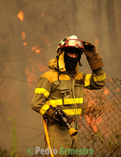 A member of the Galician fire brigade walk around the fire area in Os Anxeles, in Brion, on August 16, 2010, near A Coruna.  Pedro ARMESTRE