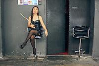 """TAI01. BANGKOK (TAILANDIA), 22/02/2011.-Meretriz frente a un local sadomasoquista en Patpong. Cientos de prostitutas en los llamados """"barrios rojos"""" de Tailandia aprenden idiomas, informática y hasta baile flamenco con ayuda de activistas que reivindican la """"dignidad"""" de esta profesión, catalogada como la más antigua del mundo. """"Tenemos centros educativos en once provincias, donde las trabajadoras sexuales aprenden idiomas, cocina o canto, así como los derechos que tienen como personas"""", explica a Efe Chantawipa Apisuk, fundadora de la organización no gubernamental Empower, comprometida con la asistencia a este colectivo. En la sede de esta organización situada en Patpong, la zona de burdeles más conocida de Bangkok, Apisuk o """"Noi"""", como le conocen sus alumnas, da a medio centenar de prostitutas una charla sobre los orígenes del Día Internacional de la Mujer, que se celebrará el próximo 8 de marzo. EFE/Gaspar Ruiz-Canela ."""