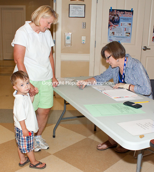 WOODBURY CT.-22 AUGUST 2013 082213DA05- Susan Flaherty along side of her grandson Jackson Dayton checks in to vote with the help of election official Martha Sherman at the Woodbury Senior Community Center Thursday afternoon. This is the fourth time voters go to the polls for a budget referendum. <br /> Darlene Douty Republican American