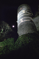 One of the corner towers The imposing Chateau d'Angers castle at night with the moon behind it. Built with black and white stone so that it looks striped, centre Maine et Loire France