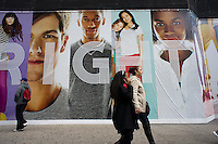 Shoppers pass a promotion for a Gap clothing store, covering its windows while the store is renovated, seen in Herald Square in New York on Saturday, February 18, 2012.  (© Richard B. Levine)