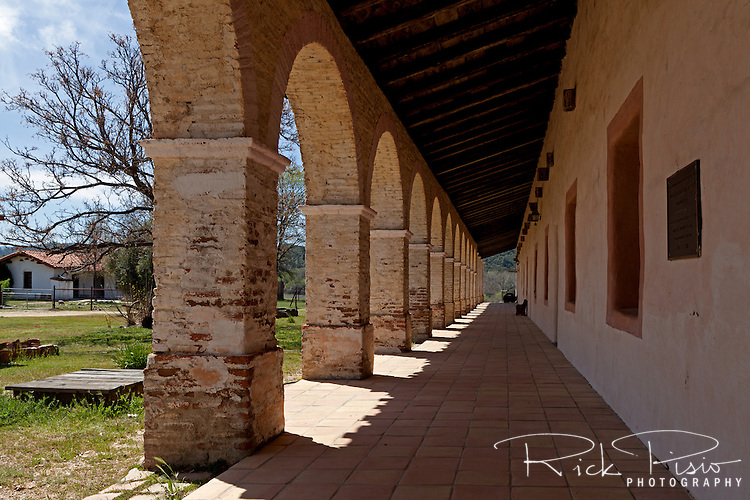 """Exterior arcade with Roman half round arches at Mission San Antonio de Padua. Mission San Antonio de Padua sits within the """"Valley of the Oaks"""" in Monterey County near the town of Jolon. The mission was founded on July 14, 1771 by Father Junipero Serra and was the third mission in Alta California. Mission San Antonio de Padua is located on eighty pristine acres on what was once the Milpitas Unit of the Hearst Ranch and is today surrounded by the Army's Fort Hunter Ligget Military Reservation."""