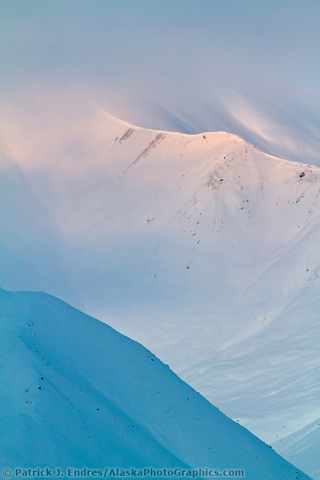 Morning light falls on the snow covered mountains in the Brooks Range, Arctic, Alaska.