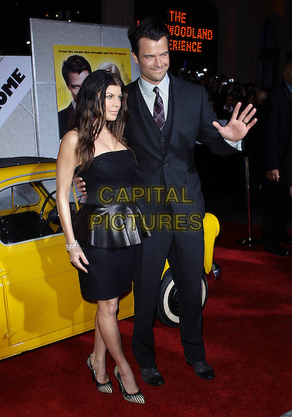 "FERGIE (STACY FERGUSON) & JOSH DUHAMEL .Attending the Los Angeles Premiere of ""When In Rome"" held at The El Capitan Theater, Hollywood, CA, USA, .27th January 2010..arrivals full length leather peplum dress strapless black cream striped shoe hand suit tie married couple husband wife grey gray .CAP/ADM/TC.©T. Conrad/AdMedia/Capital Pictures."