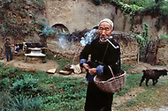 September, 1985. Shaanxi Province, China. The caves of Yan'an are more than 500 years old and still provide shelter for the farmers. Behind that man a donkey grinds grain to make flour.