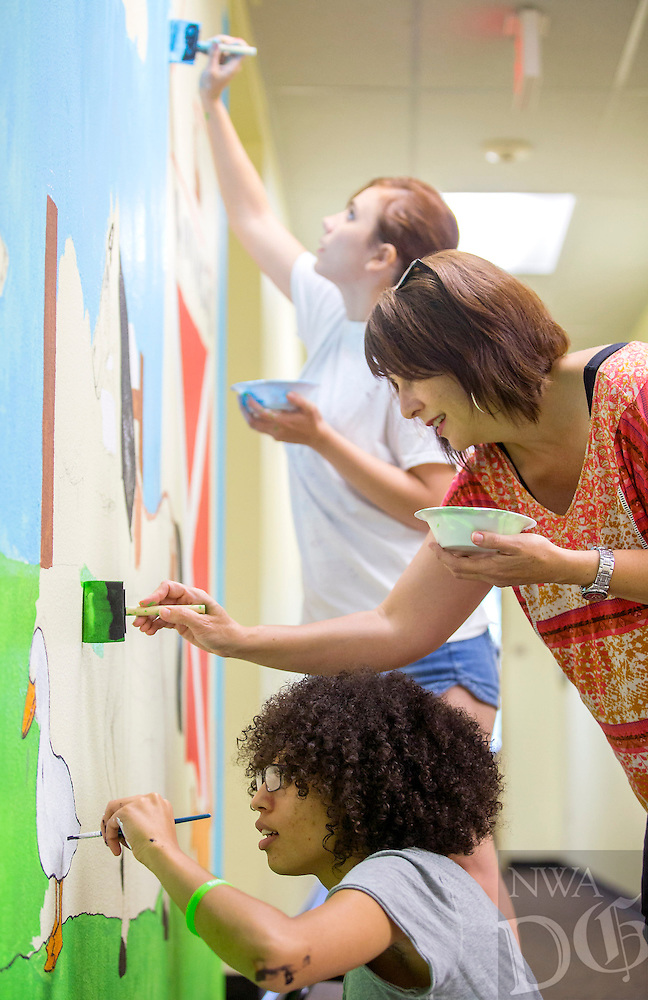 NWA Democrat-Gazette/JASON IVESTER <br /> Angie Franks (from bottom), Kelly Zega and Haley Zega work on a mural on Thursday, Aug. 6, 2015, inside the Northwest Arkansas Sunshine School and Development Center in Rogers. The mural is part of the GISHWHES (Greatest International Scavenger Hunt the World Has Ever Seen) which is an annual week-long event promoting charity work.