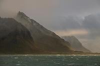 Mountain peak rises out of clearing autumn storm, Flakstadøy, Lofoten Islands, Norway