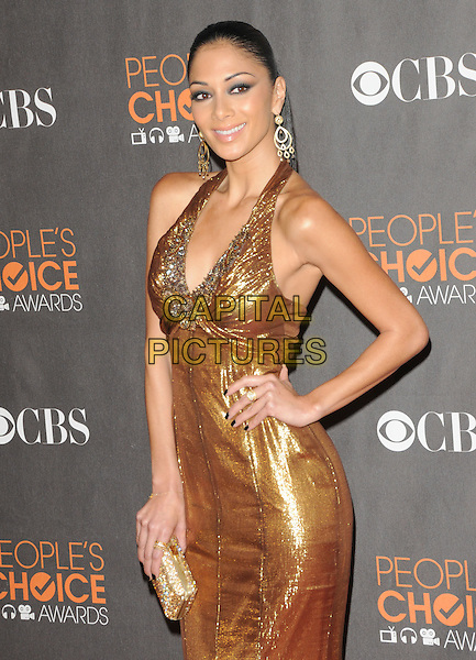 NICOLE SCHERZINGER.Arrivals at the 2010 People's Choice Awards held at the Nokia Theater L.A. Live in Los Angeles, California, USA. .January 6th, 2010.half length gold dress metallic halterneck hand on hip clutch bag dangling earrings.CAP/RKE/DVS.©DVS/RockinExposures/Capital Pictures.