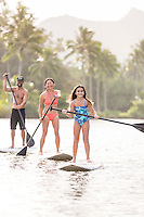A family enjoys a standup paddling lesson on Wailua River, Kaua'i.
