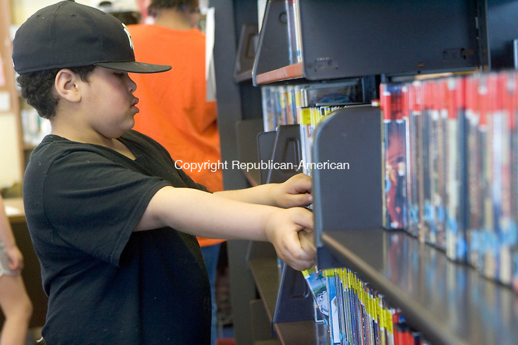 WATERBURY, CT- 21 APRIL 07- 042207JT17-<br /> Zachary Calderon, 7, peruses through the selection of DVDs at the Bunker Hill branch of the Silas Bronson Library in Waterbury on Saturday, April 21. <br /> <br /> Josalee Thrift Republican-American
