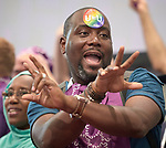 """A man dances during a July 25 activity in the Global Village of the 2018 International AIDS Conference in Amsterdam, Netherlands. He is wearing a """"U Equals U"""" sticker on his face, which celebrates new research that shows that HIV positive people with undetectable viral loads cannot transmit the disease through sex."""