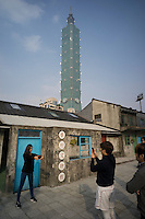 Taiwanese youths take pictures at the Museum of Military Dependents' Village against a backdrop of the Taipei 101 skyscraper in Taipei, Taiwan, 2015. A military dependents village is a community in Taiwan built in the late 1940s and the 1950s whose original purpose was to serve as provisional housing for soldiers of the Republic of China Armed Forces and their dependents from mainland China after the Government of the Republic of China (ROC) and the Kuomintang (KMT) retreated to Taiwan in 1949. They ended up becoming permanent settlements, forming distinct cultures as enclaves of mainlanders in Taiwanese cities.