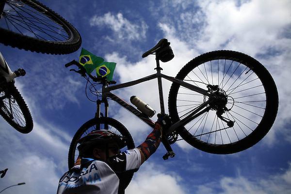 BRA516. BRASILIA (BRASIL), 15/03/2015.- Un hombre levanta una bicicleta durante una manifestación contra la presidenta brasileña, Dilma Rousseff, hoy, domingo 15 de marzo de 2015, en la ciudad de Brasilia (Brasil). Cientos de miles de personas protestaron contra la presidenta Dilma Rousseff, en Brasilia, en el marco de una jornada de manifestaciones convocadas en decenas de ciudades de todo el país. La protesta de Brasilia comenzó a las 9.30 hora local (12.30 GMT) en la explanada de los ministerios y llegó hasta la frente del Congreso Nacional Brasileño, con la participación de grupos de ciudadanos opositores sin vínculo declarado con partidos políticos. Los manifestantes corearon consignas contra Rousseff y el oficialista Partido de los Trabajadores (PT) y en rechazo de la corrupción. EFE/Fernando Bizerra Jr.