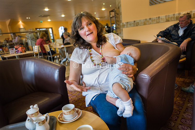 A mother talking while breastfeeding her baby in a cafe.<br /> <br /> 11 August 2011<br /> Dorset, England, UK