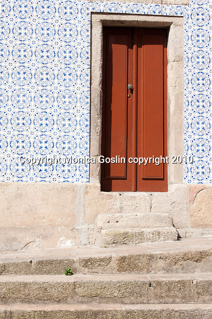 Stone steps leading up to a door of a house covered in blue and white tiles in Porto, Portugal.