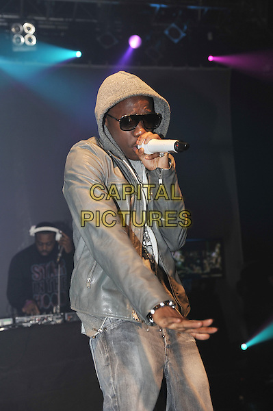 Tinchy Stryder (Kwasi Danquah).performing at the SBTV Christmas Party, Koko, Camden, London, England..21st December 2011.on stage in concert live gig performance half length grey gray hood hoodie leather jacket singing sunglasses shades  .CAP/MAR.© Martin Harris/Capital Pictures.