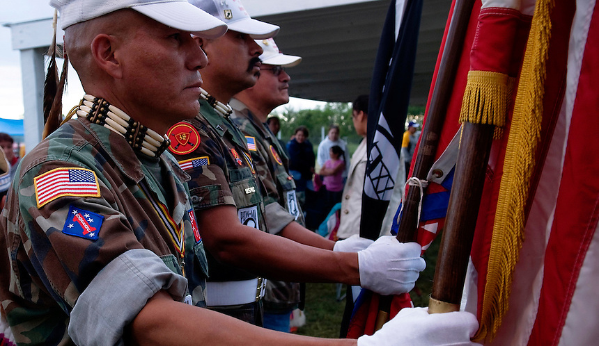 Lakota veterans from different wars, decorated with eagle feathers, symbol of bravery, holding American, MIA and Lakota flags, at the opening of the Veteran POW wow in Pine Ridge Indian Reservation, SD.