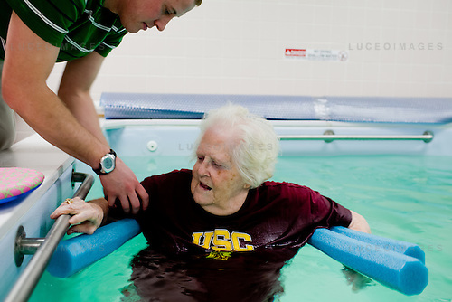 Nursing home resident Ruth Hatfield is lowered into the hospital's therapy pool for exericises.  ..One Doctor Town.  Scobey, Montana.  ..Scobey, Montana represents a small demographic of U.S. towns that is separated from major medical facilities by hundreds of miles.  More than 300 miles from the nearest large facility in Billings, Montana, Scobey's needs are tended to by Dr Sawdey.  Sawdey's  role is unique in a field where doctors tend to specialize in niche medicine; he runs the town's nursing home, attends in the emergency room consults in a family practice, does home visits for patients unable to come to the town's hospital, practice's sports medicine for the school's teams, and consults via video conference with specialists off-site.