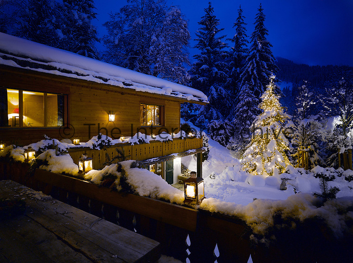 An illuminated pine tree strikes a festive note in the centre of the snow-covered garden