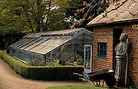 A wheelbarrow at the front of a brick shed with a long glass greenhouse behind