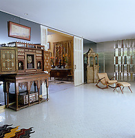 An Oriental shrine displaying a collection of sculptures in a large living room with a tiled floor and mirrored walls