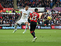 SWANSEA, WALES - FEBRUARY 21: L-R Wayne Routledge of Swansea gets the ball past Antonio Valencia of Manchester during the Barclays Premier League match between Swansea City and Manchester United at Liberty Stadium on February 21, 2015 in Swansea, Wales.