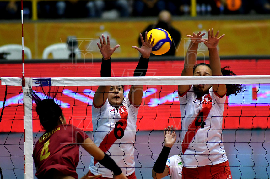 BOGOTÁ-COLOMBIA, 09-01-2020: Alexandra Muñoz y Maricarmen Guerrero de Perú, intentan un bloqueo al ataque de balón a Winderlys Medina de Venezuela, durante partido entre Perú y Venezuela, en el Preolímpico Suramericano de Voleibol, clasificatorio a los Juegos Olímpicos Tokio 2020, jugado en el Coliseo del Salitre en la ciudad de Bogotá del 7 al 9 de enero de 2020. / Alexandra Muñoz and Maricarmen Guerrero from Peru, trie to block the attack the ball to Winderlys Medina from Venezuela, from Venezuela, during a match between Venezuela and Peru, in the South American Volleyball Pre-Olympic Championship, qualifier for the Tokyo 2020 Olympic Games, played in the Colosseum El Salitre in Bogota city, from January 7 to 9, 2020. Photo: VizzorImage / Luis Ramírez / Staff.