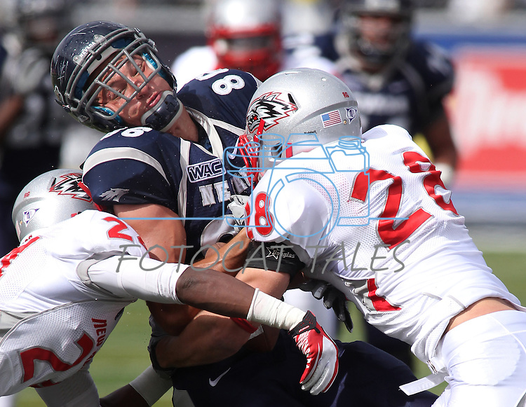 New Mexico defenders Destry Berry, left, and Bubba Forrest tackle Nevada tight end Kolby Arendse in the first quarter of an NCAA college football game in Reno, Nev., on Saturday, Oct. 15, 2011. (AP Photo/Cathleen Allison)