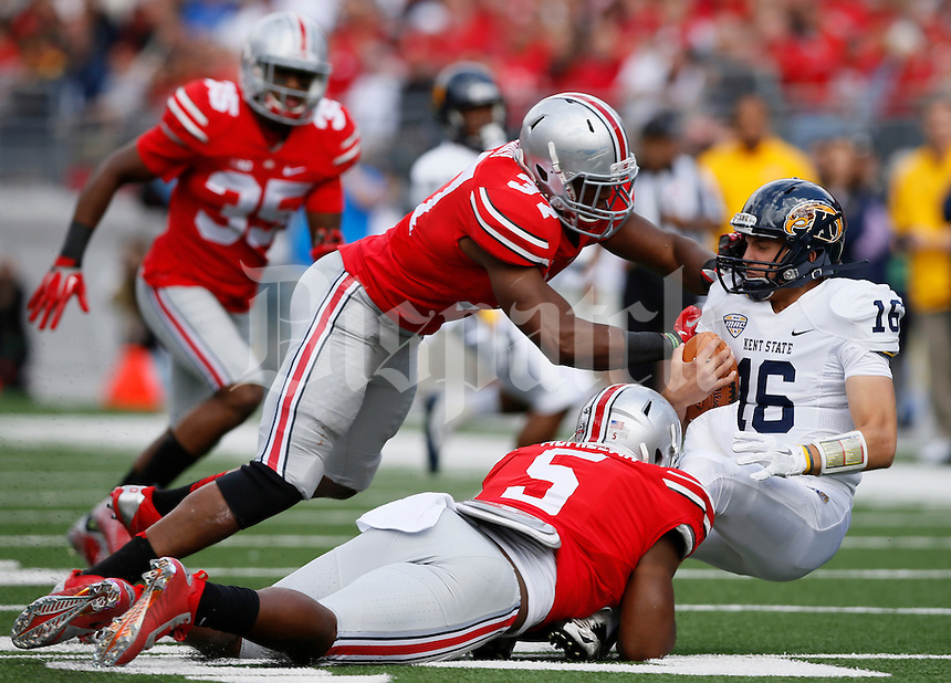 Kent State Golden Flashes quarterback Nathan Strock (16) is sacked by Ohio State Buckeyes linebacker Joshua Perry (37) and Ohio State Buckeyes linebacker Raekwon McMillan (5) during Saturday's NCAA Division I football game at Ohio Stadium in Columbus on September 13, 2014. (Dispatch Photo by Barbara J. Perenic)