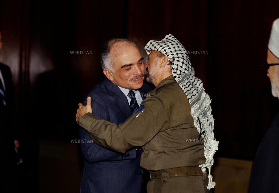 1984. Jordan. Amman. King Hussein of Jordan (1935-1999) embraces Yasser Arafat (1929-2004), chairman of the PLO, on his arrival for the 17th meeting of the Palestinian National Council (PNC). Jordanie. Amman. Le Roi Hussein de Jordanie (1935-1999) embrasse Yasser Arafat (1929-2004), le chef de l'OLP, à son arrivée pour la 17e réunion du Conseil National Palestinien (CNP).