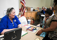 NWA Democrat-Gazette/CHARLIE KAIJO Volunteer Kay Jones (left) reacts as she sells books to Inesh Vasireddy, 8, and Anitha Verneni of Bentonville (right) during a book sale, Thursday, October 4, 2018 at the Bentonville Public Library in Bentonville.<br />