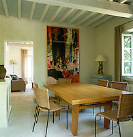 The simple dining room is linked to the living room by a floor of untreated travertine and is dominated by a painting by Francesco Frangi