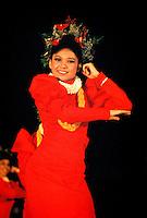 Woman with red muumuu performing Auana hula, a modern form.