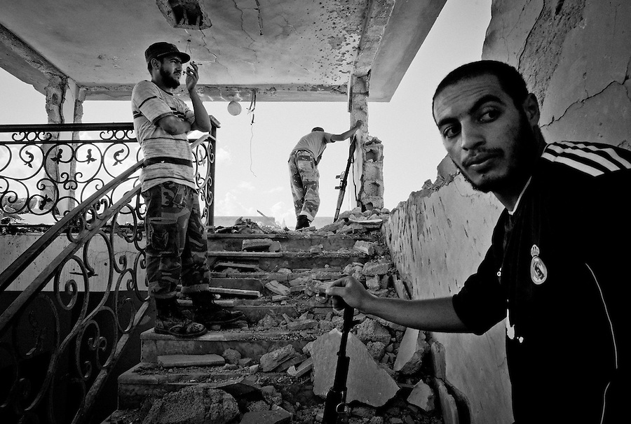 Anti-Gaddafi fighters survey Gaddafi loyalist positions in Sirte, Libya.