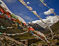 Prayer flags wave in the wind in the upper Drolma Valley, a high country valley north of Lhasa, Tibet.