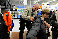 NWA Media/ J.T. Wampler - Kevin East, a sergeant with the Washington County Sheriff's office, helps Christopher Easter, 8, of Greenland try on a coat Friday Dec. 5, 2014. The department's Shop With A Cop program provides selected children from area school districts with an all expense paid shopping trip with a uniformed officer for clothes, toys and more.