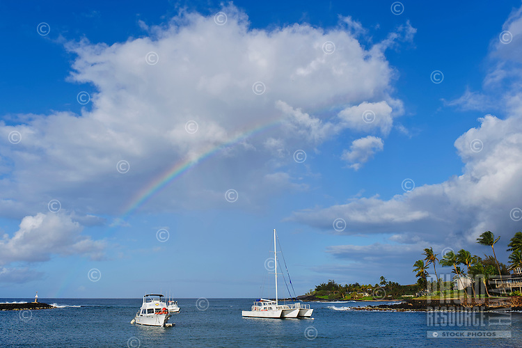 A rainbow over Kukui'ula Harbor, Kaua'i.