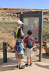 Mother and children look at information sign in Arches National Park, Moab, Utah, USA. .  John offers private photo tours in Arches National Park and throughout Utah and Colorado. Year-round.