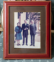BNPS.co.uk (01202 558833)<br /> Pic: PhilYeomans/BNPS<br /> <br /> Thomas with his parents at the Palace.<br /> <br /> A remarkable 'timewarp' archive amassed by a dressmaker to the Queen has sold for over £100,000.<br /> <br /> The late Ian Thomas meticulously kept his fashion designs, letters, cards and photographs relating to the Queen at his home that was more like a museum. <br /> <br /> He helped design the Queen's coronation gown in 1953 as well as the powder blue outfit she wore for Charles and Diana's wedding in 1981.<br /> <br /> The lifelong bachelor passed away in 1993 and left his home and its contents to a florist he had been good friends with for 25 years.<br /> <br /> After she died in 2015 the property was inherited by a relative who also knew Mr Thomas well.<br /> <br /> She has now sold the contents at auction.