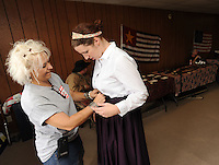 NWA Democrat-Gazette/ANDY SHUPE<br /> Kimberly Fielding Winters (left), co-owner of The Mercantile, a nearby antique store, helps Gina Billeaudeau, director of the Elm Springs Historical Society's Heritage Center, Saturday, Aug. 22, 2015, with her period costume during an open house at the center in Elm Springs. The group plans to further develop the center's offerings and to host activities in the future to celebrate the historical significance of the town.
