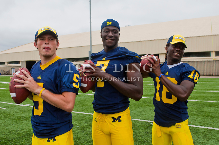 Michigan quarterbacks Tate Forcier (5), Devin Gardner (7), and Denard Robinson (16) pose for pictures at the annual NCAA college football media day, Sunday, Aug. 22, 2010, in Ann Arbor, Mich. (AP Photo/Tony Ding)