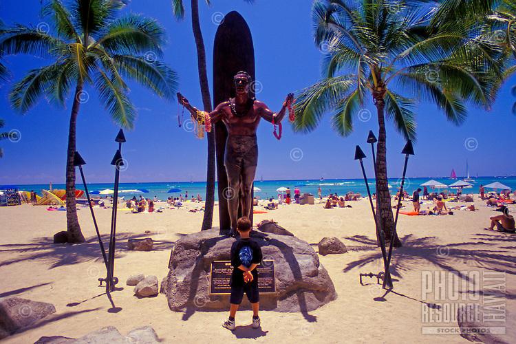 Young boy standing in front of the Duke Kahanamoku statue in Waikiki